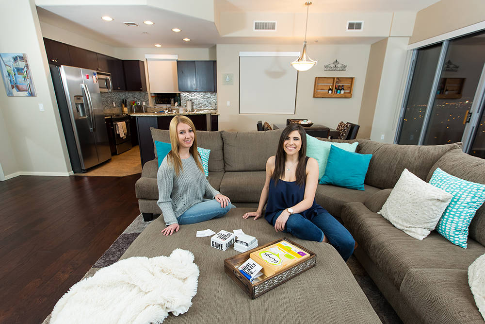 Two residents sitting in their living room and playing games at their One Las Vegas home