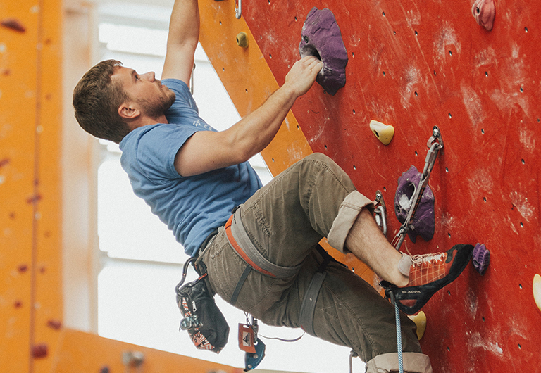 Man climbing up an indoor rock wall.