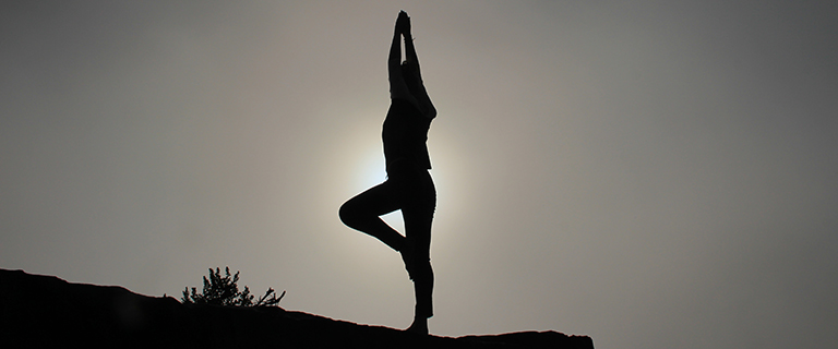 Person doing yoga pose on top of a hill, in front of the sun.