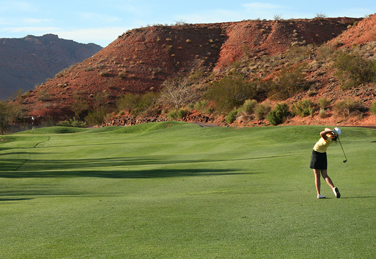 Woman taking a golf swing on a course in Las Vegas.