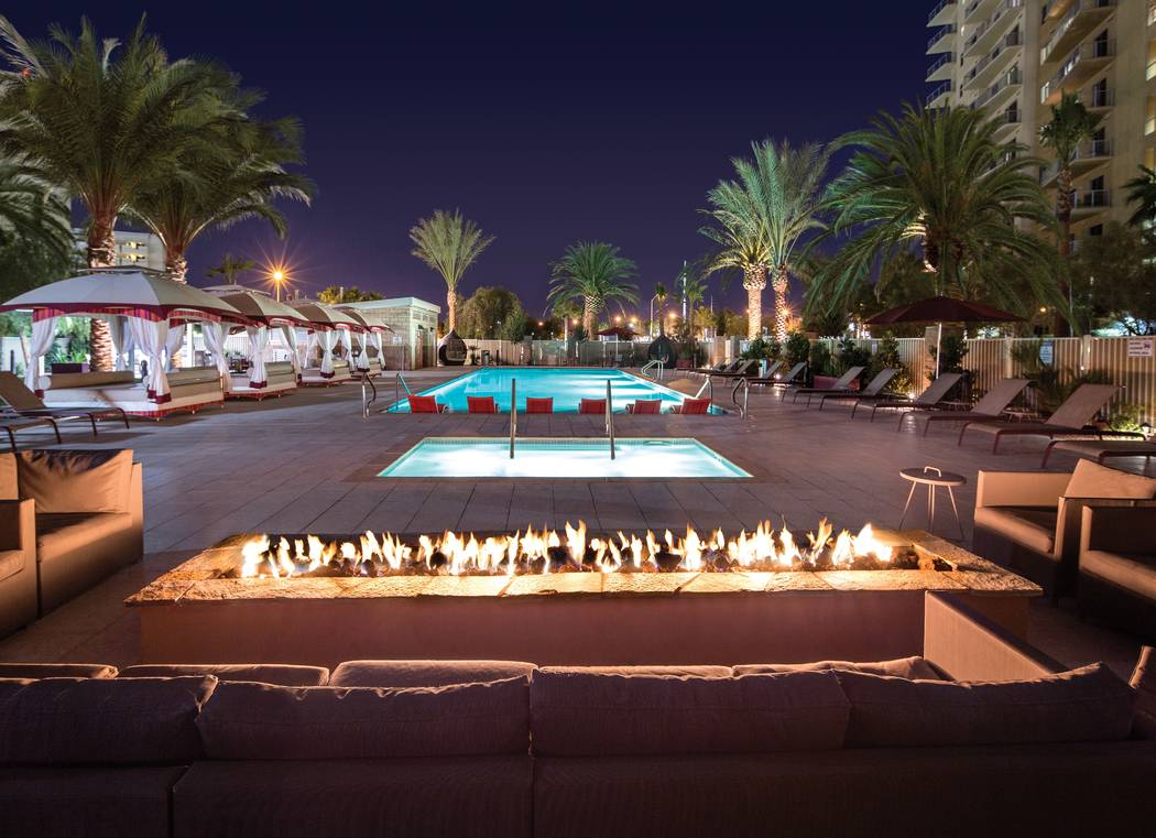 Resort style pool, cabanas, and fire pit at night at One Las Vegas