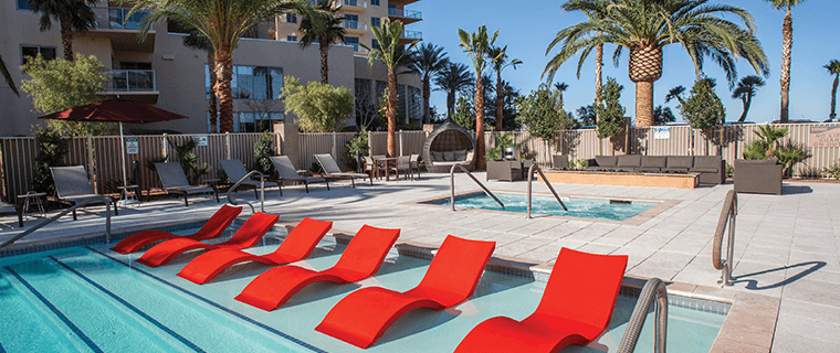 The 24-hour pool at One Las Vegas with red lounge chairs and cabanas.