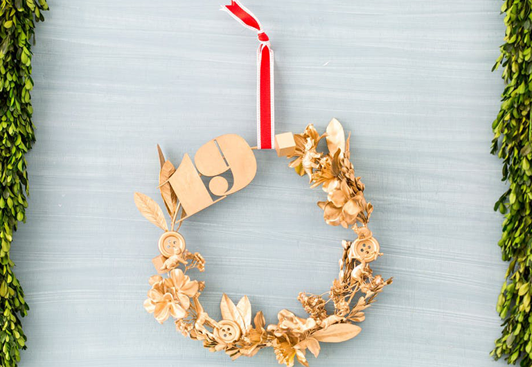 A DIY holiday decoration wreath spray painted gold and hung up.