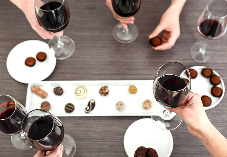 Group of friends having fun at a chocolate and wine pairing party